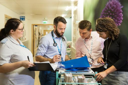 Three doctors and a nurse look at a folder of papers on a hospital ward