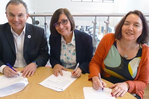 A man and two women sitting at a round table signing pieces of paper