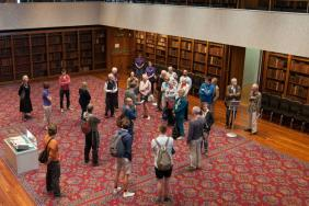 A group of people stand in a large room lined with bookcases