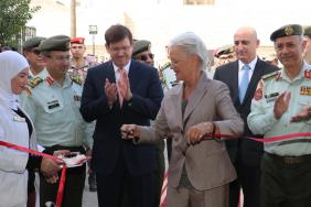 A woman cuts a red ribbon while a crowd of people applauds