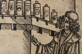 Black line woodcut illustration of two men in an apothecary shop. One is seated at a table consulting a book, the other stands, pointing with a stick towards a shelf of apothecary jars.