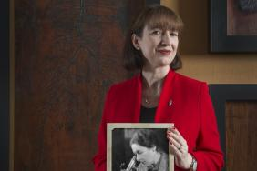 Dr Suzy Lishman holding a picture of Professor Dorothy Russell