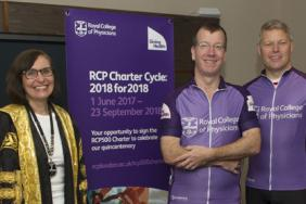 Two cyclists wearing purple stand next to the president of the Royal College of Physicians
