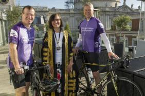 Andrew Goddard and Ian Bullock, joined by president of the RCP Professor Jane Dacre, stand with their bicycles on the roof of the Grange hotel with St Paul's Cathedral in the background