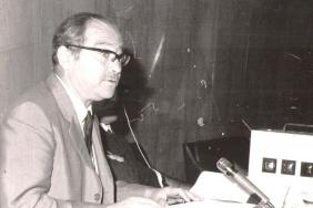 Black and white photograph of Alan Nabarro seated at a table given a conference paper.