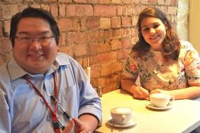 A male and a female doctor sitting in a cafe
