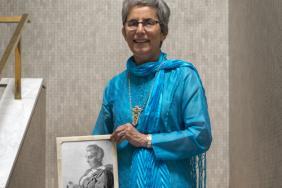 Professor Dame Parveen Kumar holding a photograph of Dr Jane Walker