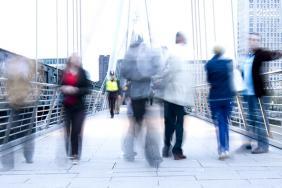 Blurred people walking over a bridge