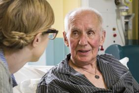 An elderly male patient in bed talks to a younger female health professional, who is showing him a bright yellow document