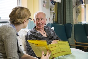 A doctor and her patient read a booklet of information