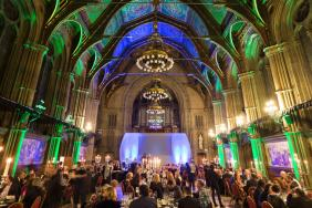 People sit at tables during a dinner ceremony held in a room with blue and green lighting and chandeliers hanging from the ceiling