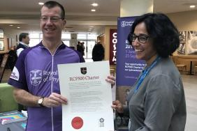 A cyclist and a doctor are smiling as they hold up a large piece of paper with a red seal