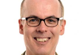 A doctor wearing spectacles smiling