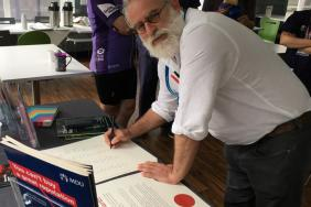 A doctor with a white beard signs a large paper document