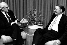 A black and white photograph of two white men sitting on low chairs, facing each other, the lens and tripod of a large video camera is visible at the right-hand edge of the photograph