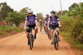 Two men ride bicycles side by side along a straight sandy road