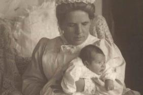 Black and white photograph of a women in Victorian nursing dress holding a small baby