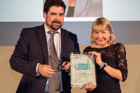 A doctor smiles as she collects an award