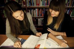 Two female medical students consult a textbook in a library